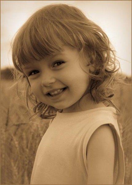 Фото Кудрявая маленькая девочка мило улыбается.